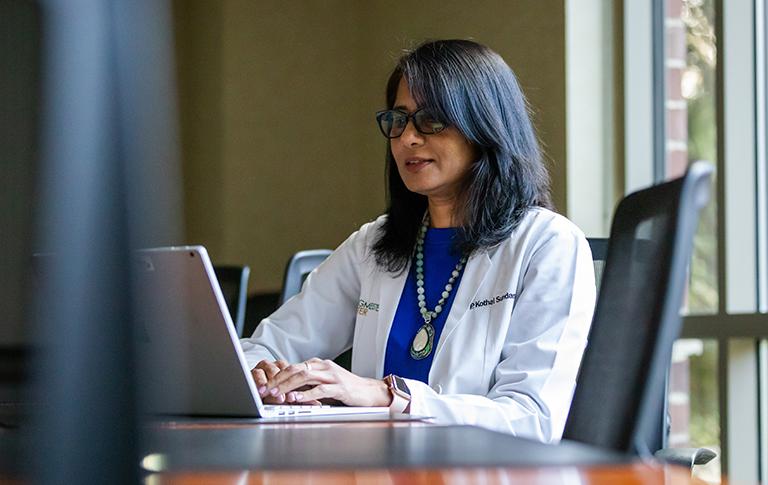 Dr. Sundaram working on laptop in her office.