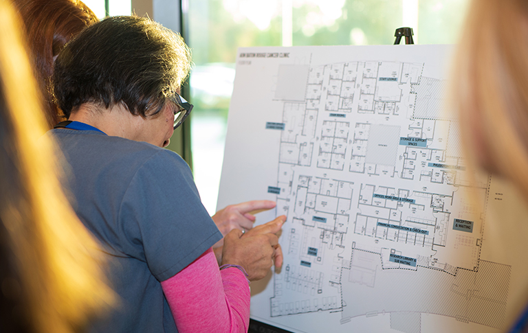 Nurse pointing to hospital map with patient.