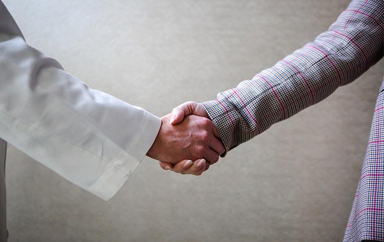 Partnership handshake between doctor and medical professional.