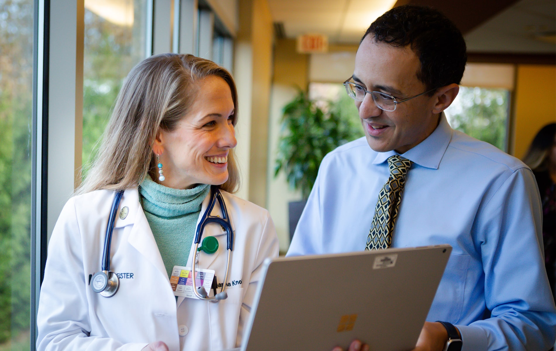 Dr. Knoble and Dr. Mikhail smiling while holding a laptop.
